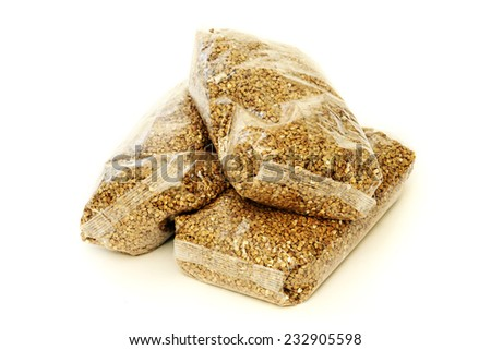 Three packs of buckwheat in transparent plastic bags - stock photo