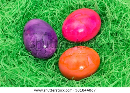 Three painted easter eggs in a nest of green grass