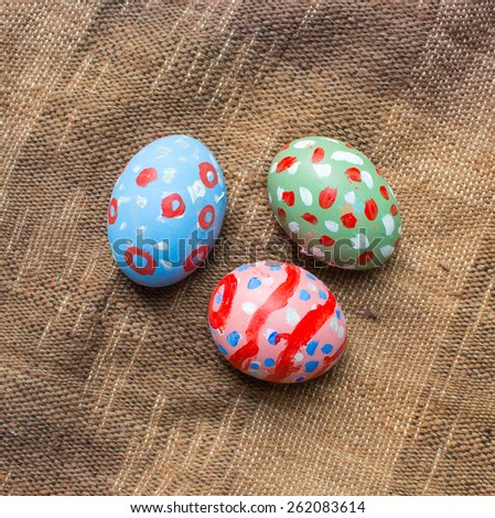 Three painted eggs for Easter on brown cotton background - stock photo