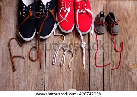 three pair of shoes in father big, mother medium and son or daughter small kid size on wooden desk , representing family, growth, education and togetherness concept