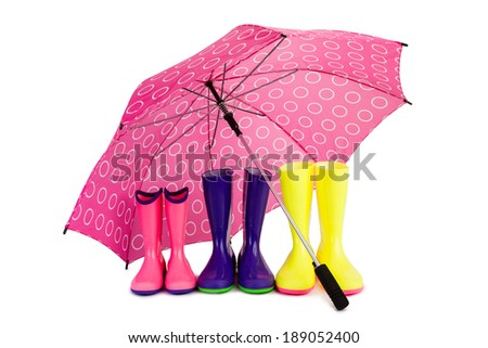 Three pairs of colorful rubber boots and big pink umbrella, isolated