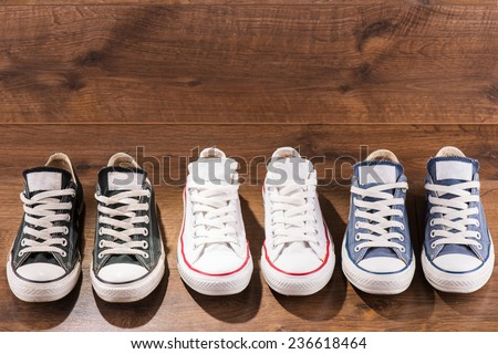 three pairs of cool youth white gym shoes with red  stripes  on brown wooden floor  standing in line with copy place  top view  - stock photo
