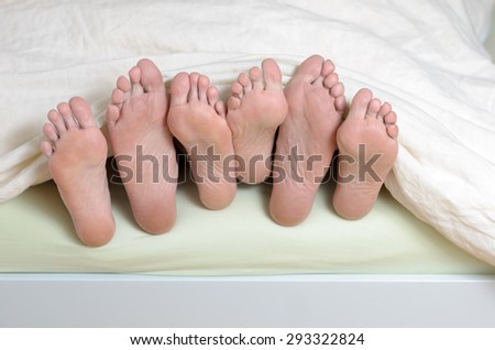 Three pairs of feet in bed, mixed up