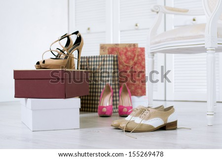 Three pairs of just purchased and unboxed shoes on a floor of a wardrobe - stock photo