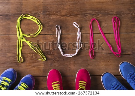 Three pairs of running shoes and shoelaces run sign on a wooden floor background - stock photo
