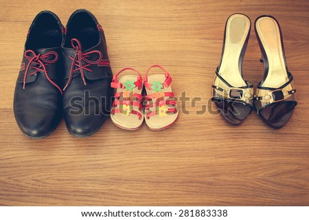 Three pairs of shoes: men, women and children. Baby sandals stand next to men's  shoes. concept of the child is friends with his father. Idea parents divorced, child remained with father. Toned image - stock photo