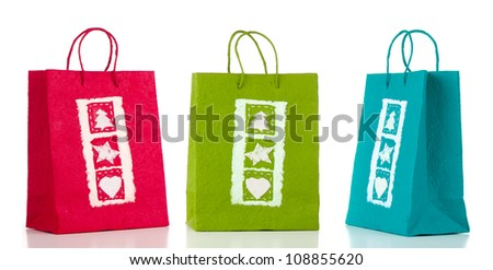 Three paper bags on white reflective background. - stock photo