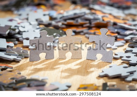 Three paper jigsaw puzzles surrounded by pieces  on a table. Shallow depth of field - stock photo