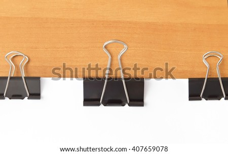 Three paperclips stapling papers on the table - stock photo