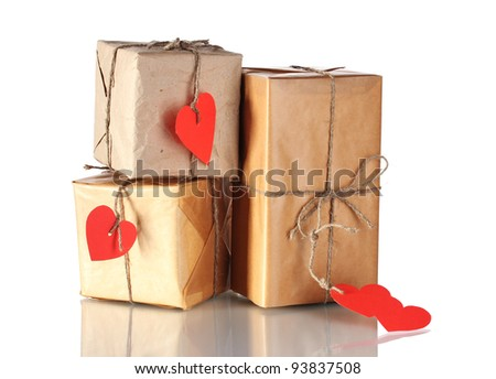 Three parcels with blank heart-shaped labels isolated on white - stock photo