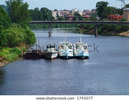 Three parked ships on a small river