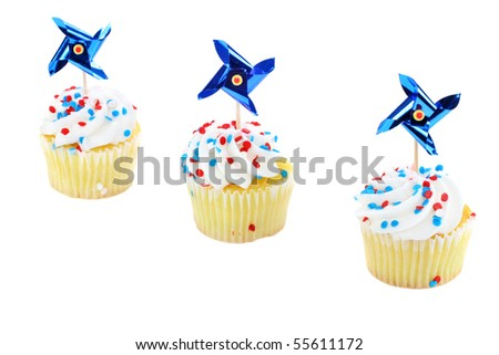 Three patriotic decorated cupcakes on a diagonal.  Red, white and blue with pinwheel decorations.