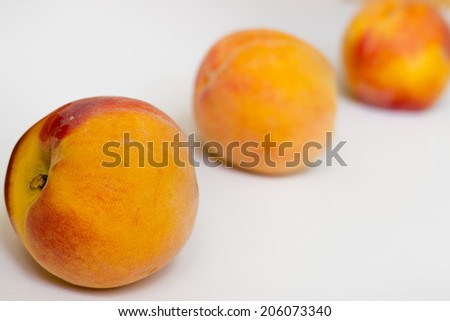 Three peaches on a white background.