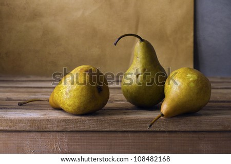 Three pears on wooden table - stock photo