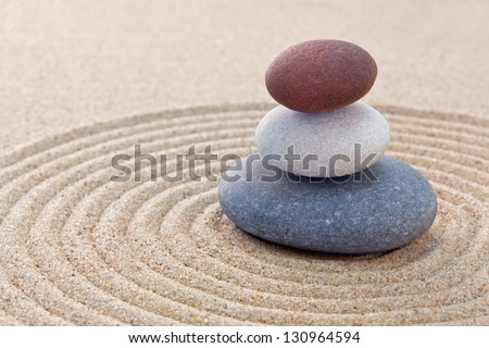 Three pebbles stacked on a circular raked zen garden - stock photo