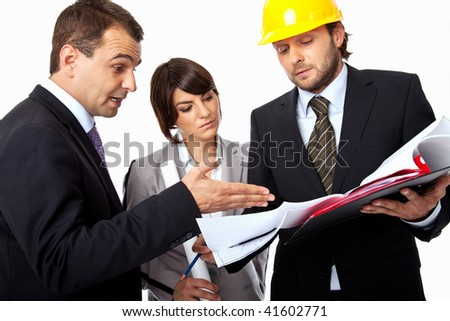 three people are arguing over a plan, one with a helmet - stock photo