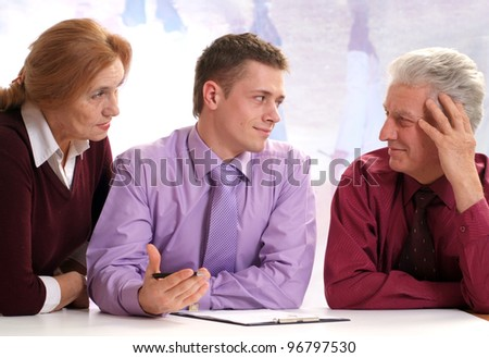 Three people are sitting on a background