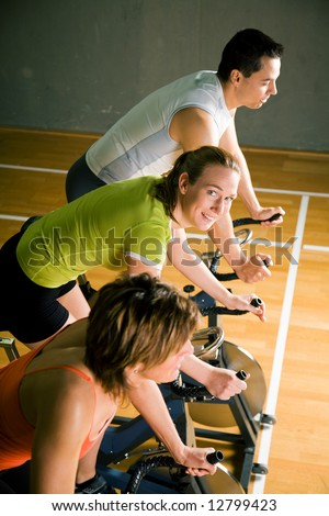 Three people cycling in a gym or fitness club, dressed in colorful clothes; focus on the girl in green in the middle