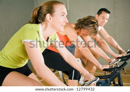 Three people cycling in a gym or fitness club, dressed in colorful clothes; focus on the girl in green in front