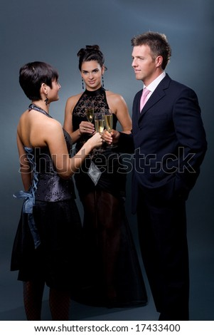 Three people drinking champagne on a party.