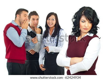 Three people gossip and joke  in background about  their colleague woman and she standing with hands crossed and looking down with a sad face