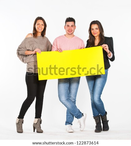 Three people holding a yellow, blank paper - stock photo