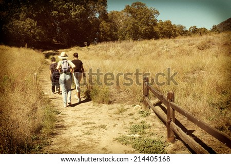 Three people on a hike in a rural setting. Mother, daughter and son walking on a rural path with a retro instagram look with vignette. - stock photo