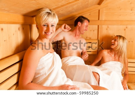 Three people (one male, two female) enjoying a hot sauna, having a casual chat - stock photo