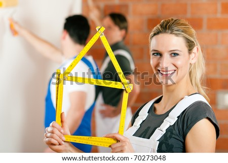 Three people - one woman and two men � renovating an apartment and having lots of fun - stock photo