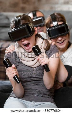three people playing a video game with console, virtual reality glasses - stock photo