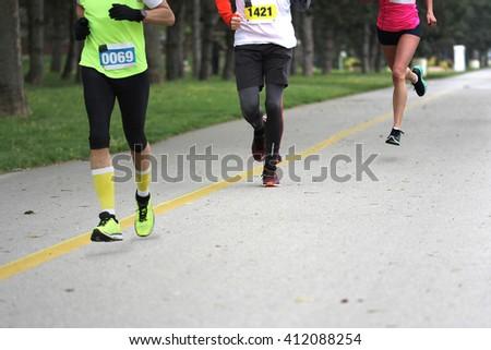 Three people running Cross country Marathon, Blured Motion  - stock photo
