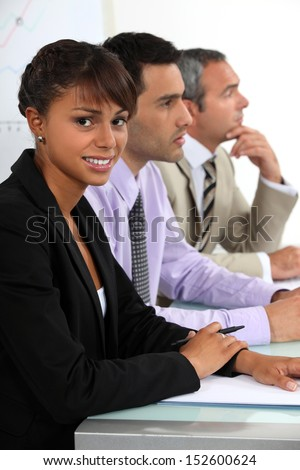 Three people sat on interview panel - stock photo
