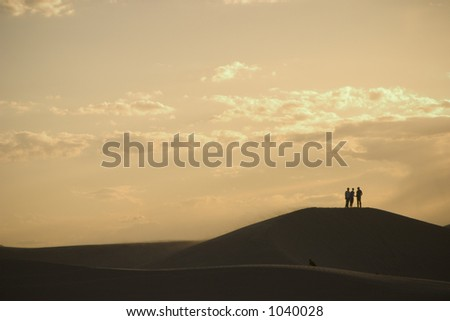 three people standing on a sand dune