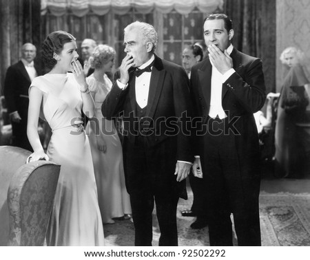 Three people standing together at a formal party yawning and being bored - stock photo
