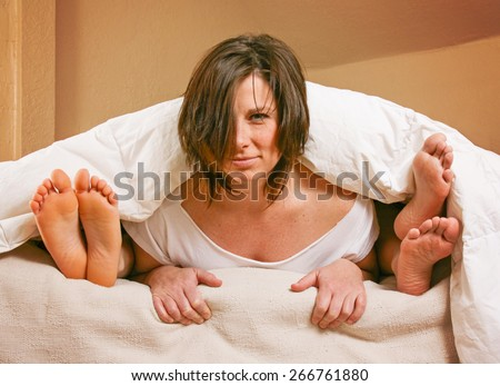 three people under the covers with feet showing in a bed  - stock photo