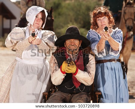 Three people with guns out in old American west scene - stock photo
