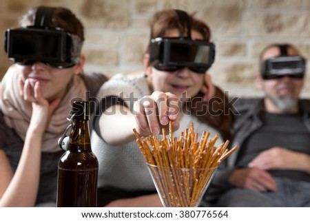 three people with virtual reality glasses and snacks, having fun