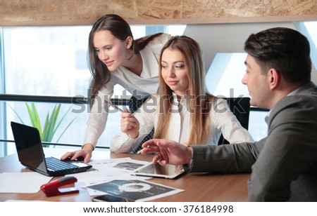 Three people work in the office on the background of a window - stock photo
