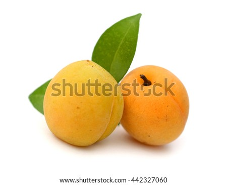 Three perfect, ripe peaches with a half isolated on a white background.