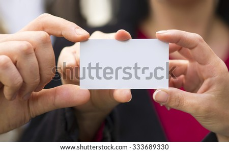three person, a businessman and two woman holding a white card together - stock photo