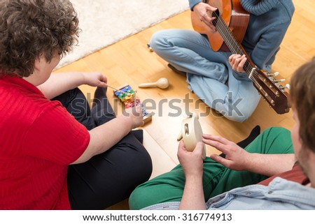 three persons playing sundry instruments at home