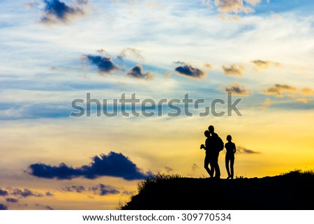 Three persons standing on the top of a hill watching sunset
