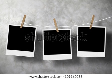 three photo paper attach to rope with clothes pins on old stone background - stock photo