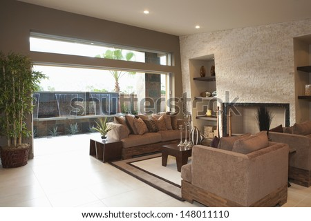 Three piece suite around coffee table in modern house - stock photo