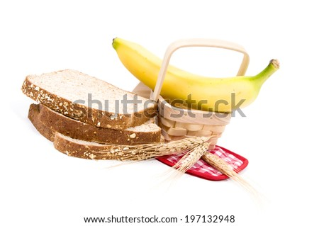 Three pieces of bread, a banana and some grain. - stock photo