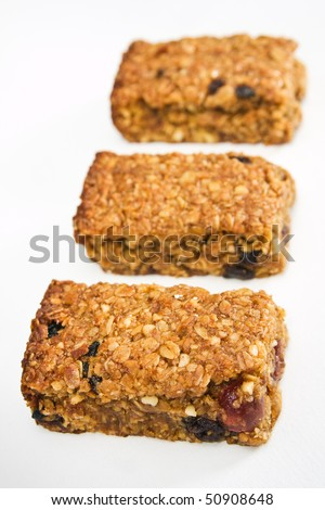 Three pieces of fresh homemade cherry and raisin flapjack, in a row on a white table cloth with short depth of field.