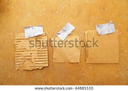 three pieces of torn grunge paper, taped to a wall - stock photo
