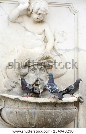 Three pigeons standing on a water fountain.