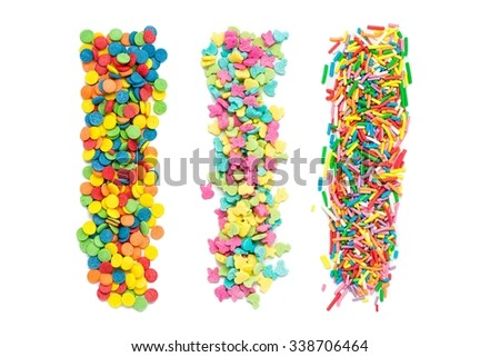 Three piles of different sugar sprinkles isolated over white - stock photo