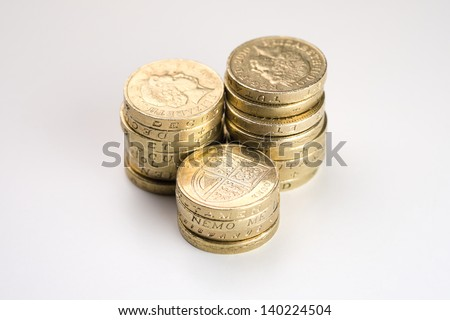 Three Piles of Pound Coins on a Table - stock photo